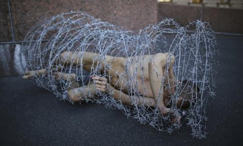 Pyotr Pavlensky lies on the ground in barbwire - photo Reuters
